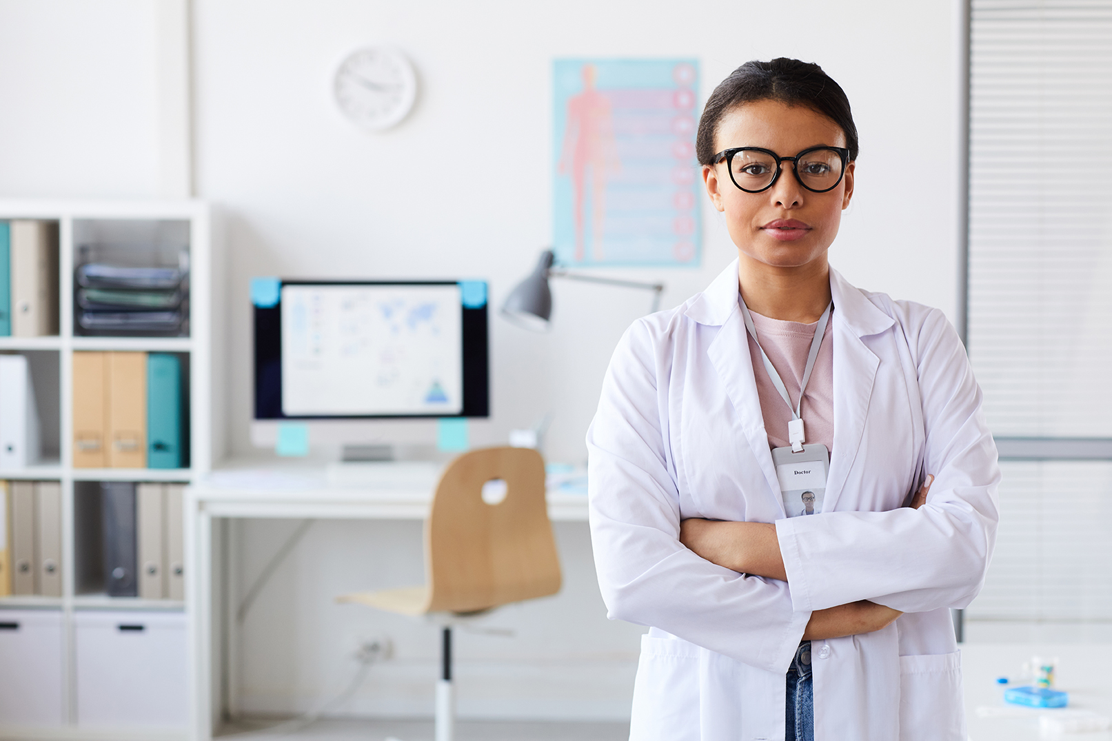 Portrait of young female doctor in eyeglasses standing with her arms crossed and looking at camera at office